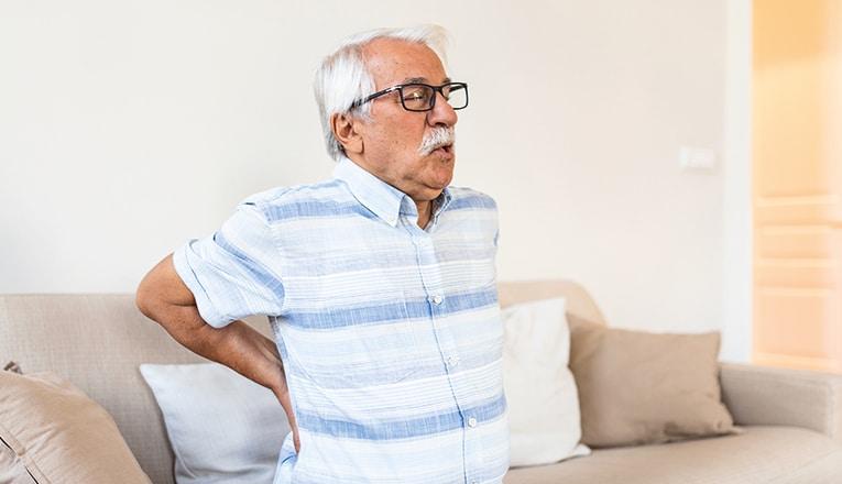 Monsieur souffre de son dos en raison d'une hernie dorsale.