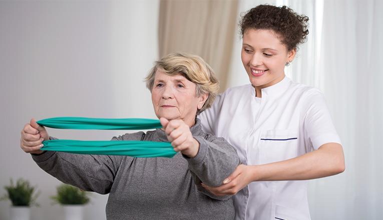 Madame fait des exercices avec un kinésithérapeute pour une hernie dorsale.